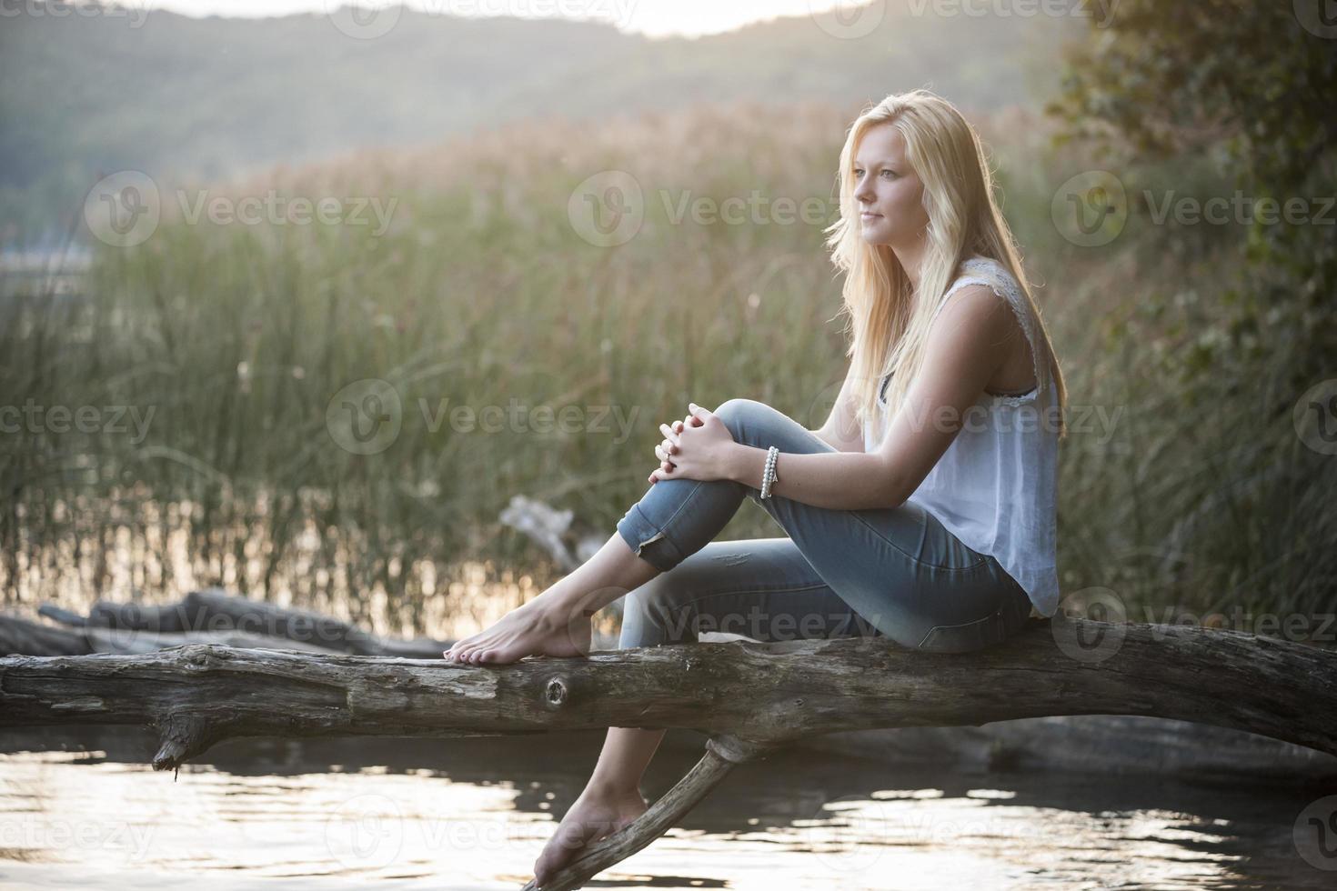 jeune femme, séance, sur, tronc arbre, à, lac photo