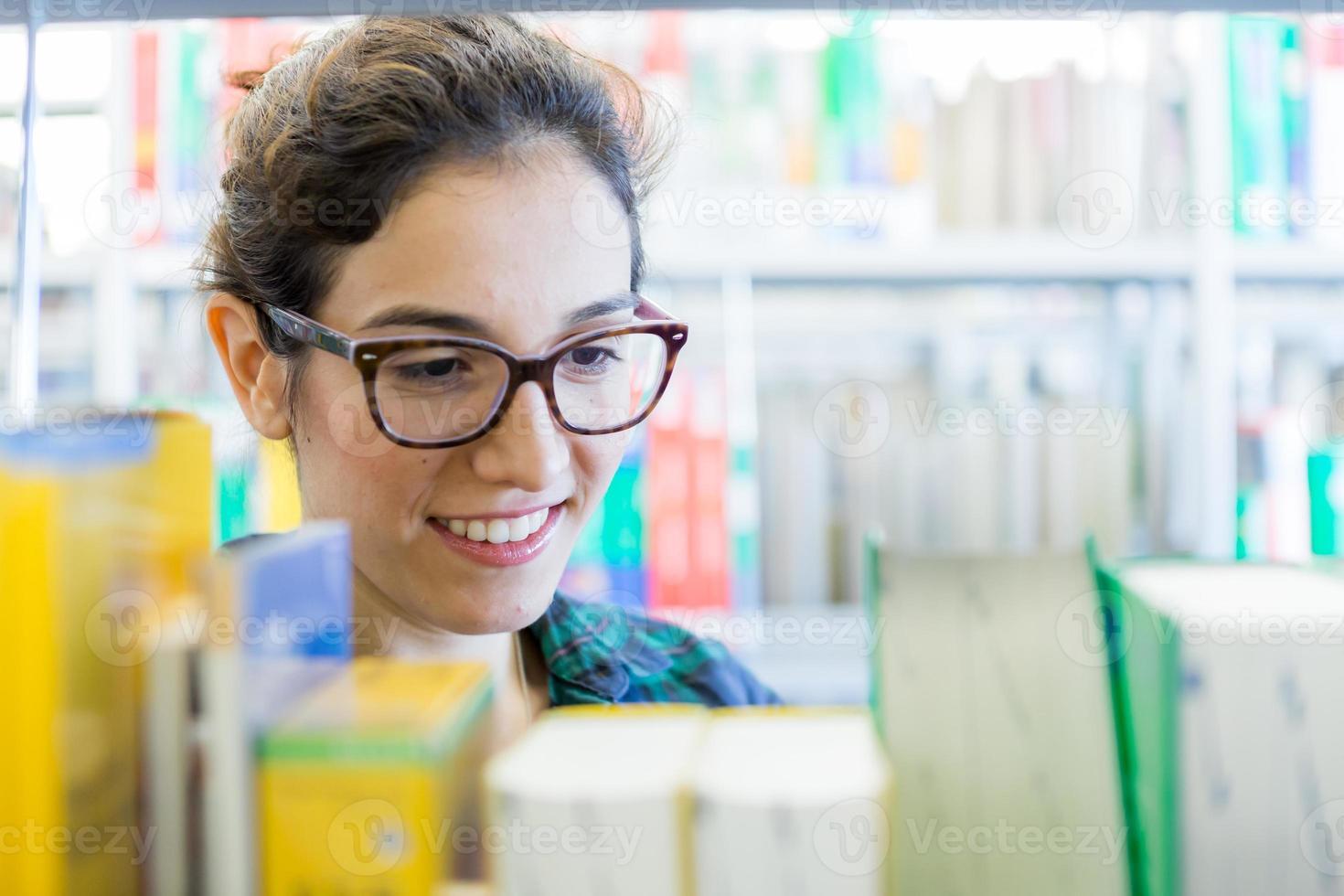 jeune étudiant à la recherche de livres à la bibliothèque photo