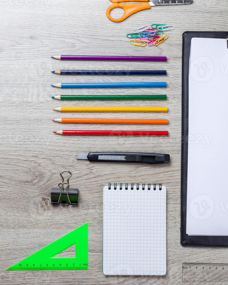papier, crayons, pinceau, pomme verte sur table en bois photo