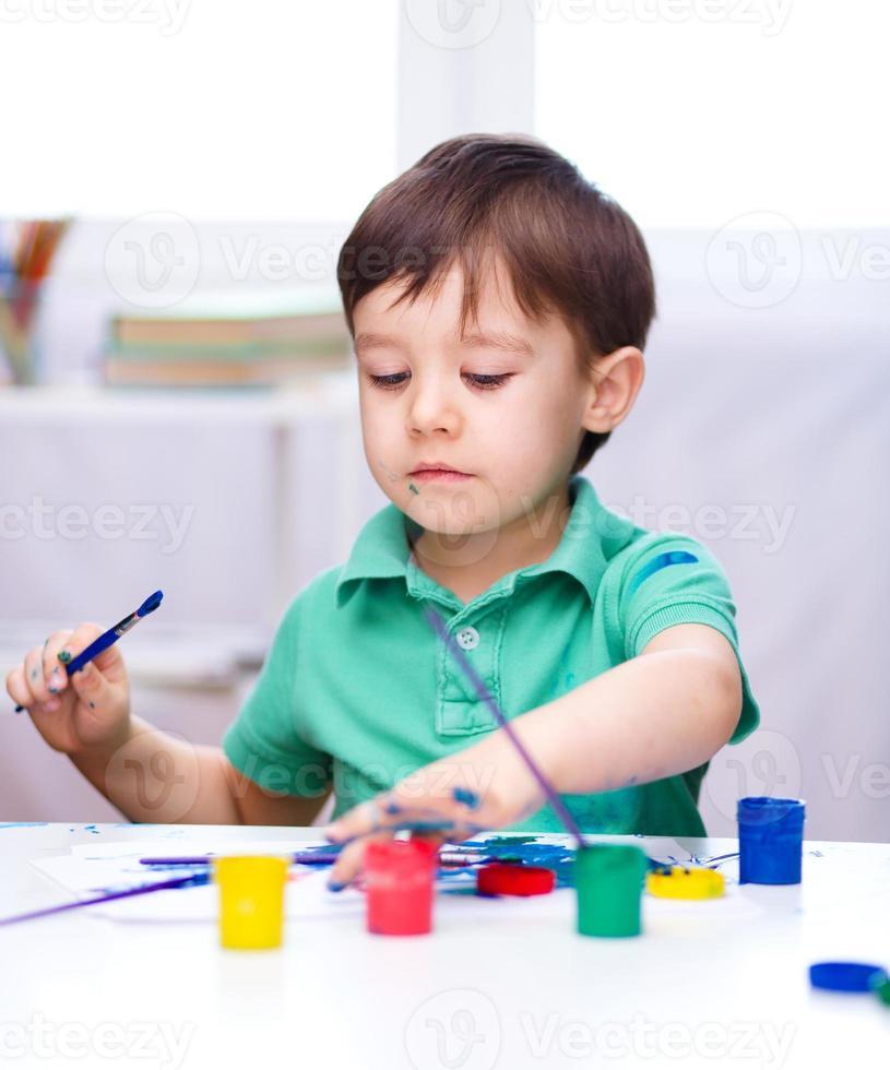 petit garçon joue avec des peintures photo