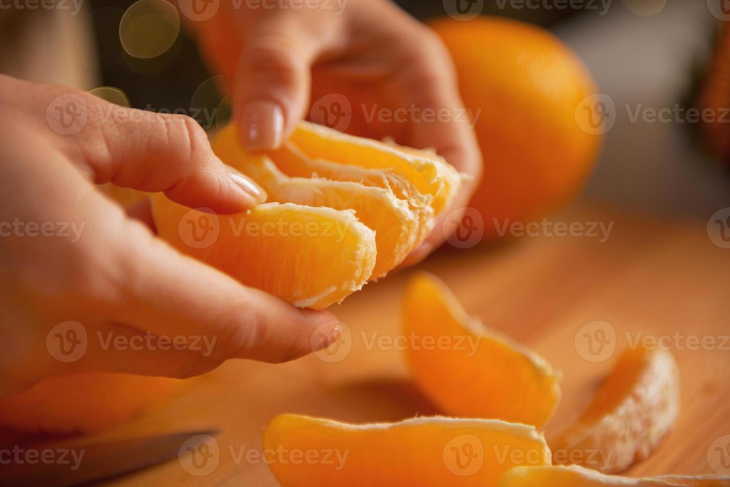 Gros plan sur la jeune femme au foyer, divisant les tranches d'orange photo