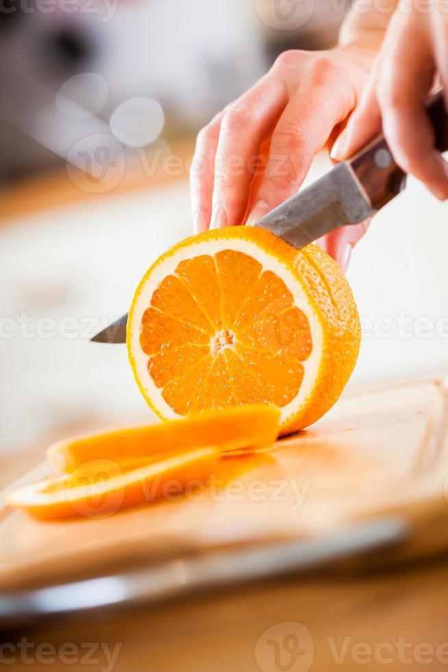 mains de femme, couper l'orange photo