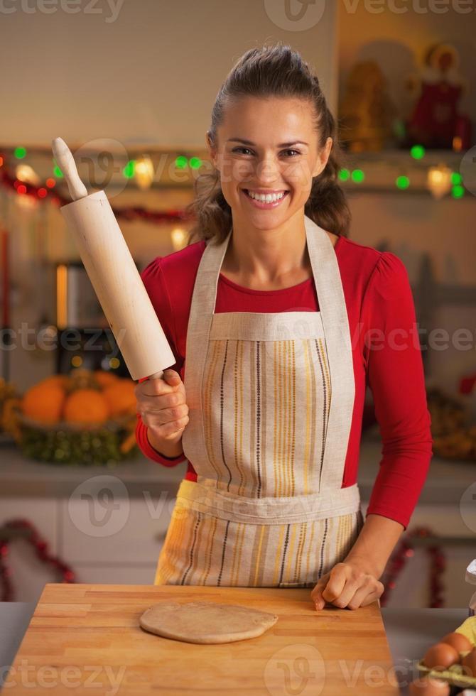 femme au foyer avec rouleau à pâtisserie dans la cuisine décorée de Noël photo