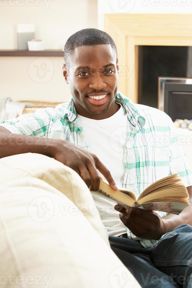 jeune homme, délassant, sur, sofa, livre lecture, chez soi photo