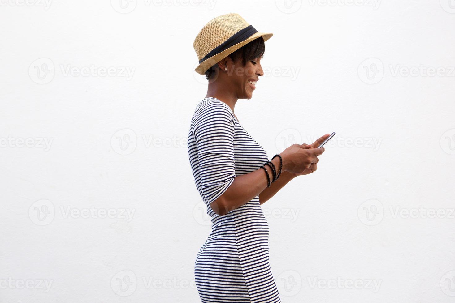 gaie jeune femme marchant et envoyer des SMS photo