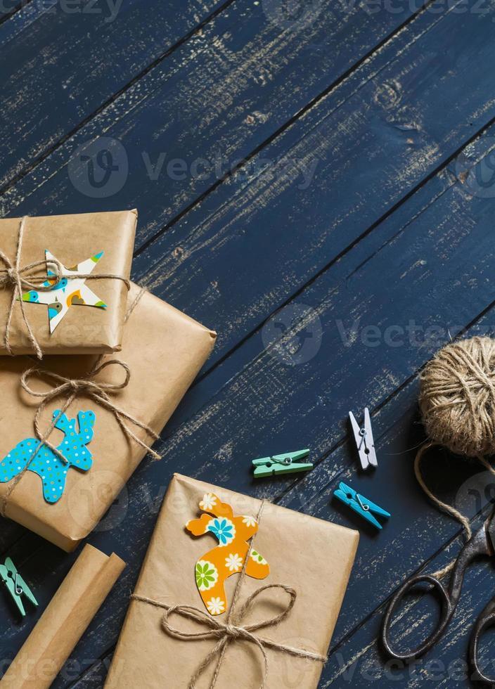 cadeaux de Noël en papier kraft sur une surface en bois sombre. photo