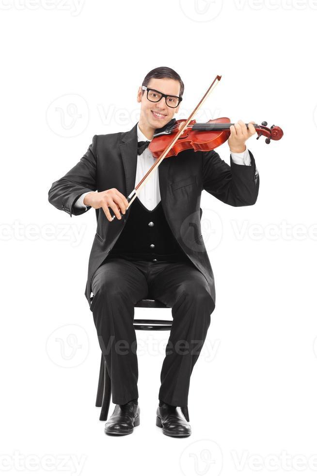 Joyeux jeune violoniste jouant du violon photo