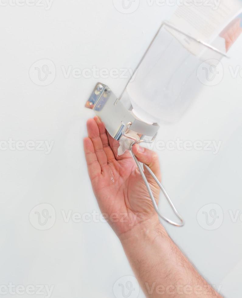 main en utilisant le distributeur de pompe de gel désinfectant pour les mains photo