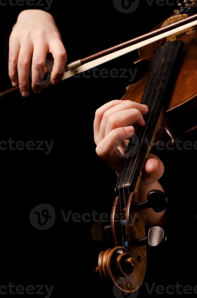 mains féminines jouent du violon sur le noir photo