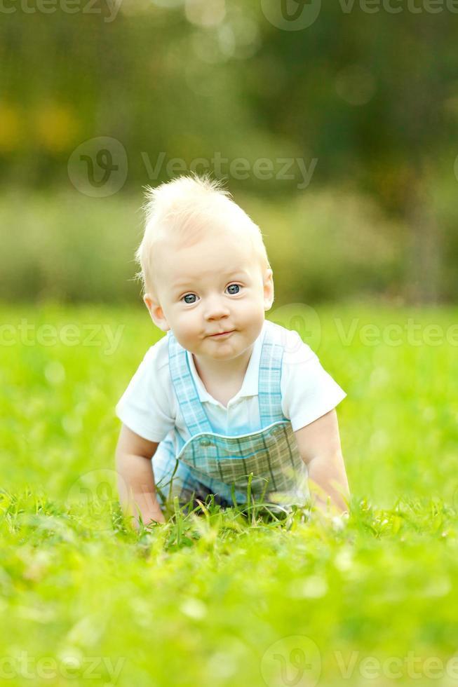 mignon petit bébé dans le parc d'été sur l'herbe. photo