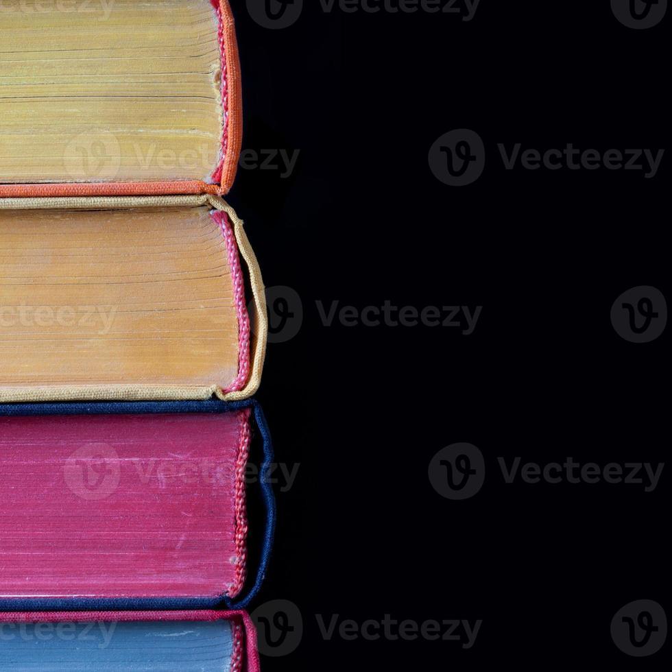 livres colorés. couverture rigide. fond noir. isolé photo