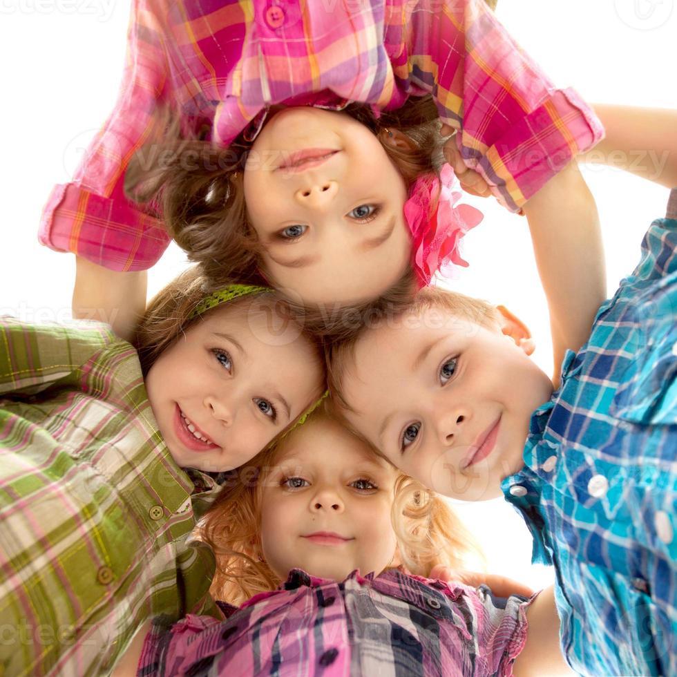 enfants heureux mignons regardant vers le bas et se tenant la main photo