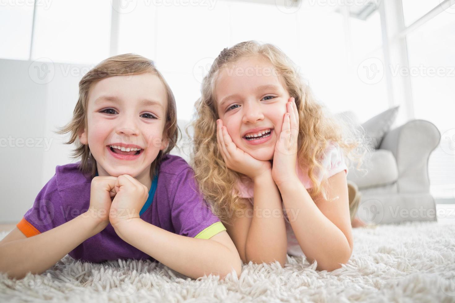 frères et sœurs heureux allongé sur un tapis à la maison photo