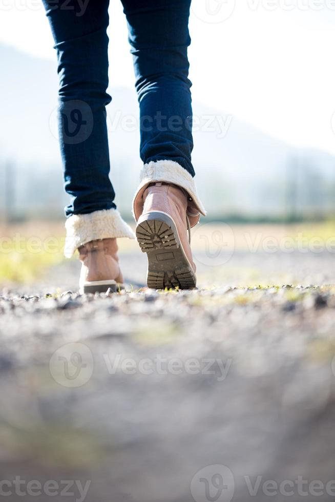 femme en jeans et bottes marchant le long d'un chemin rural photo