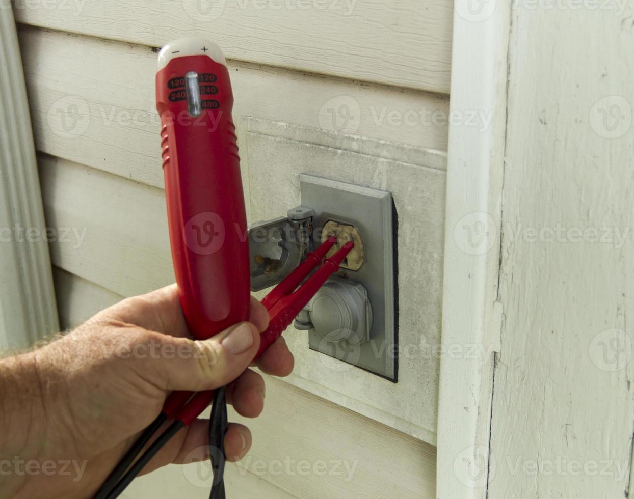 électricien testant une prise extérieure photo
