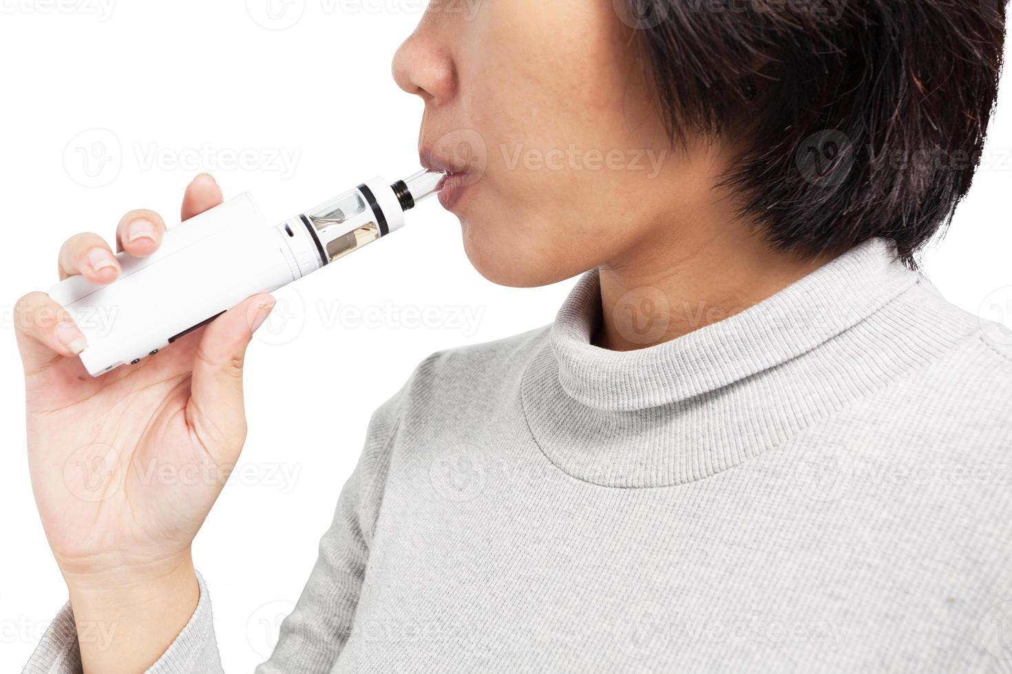femme asiatique inhalant d'une cigarette électronique. photo