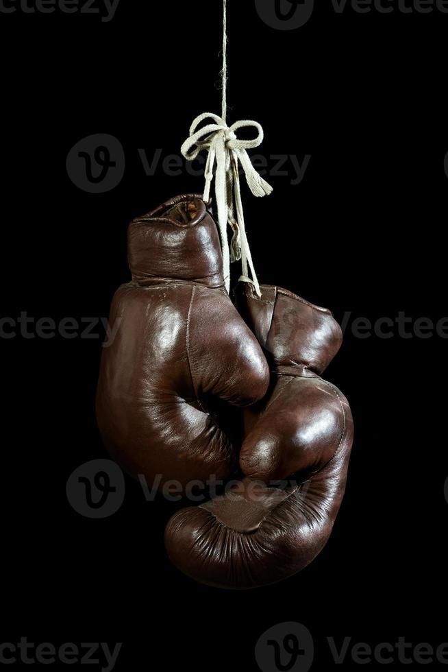 vieux gants de boxe, suspendus, isolés sur fond noir photo