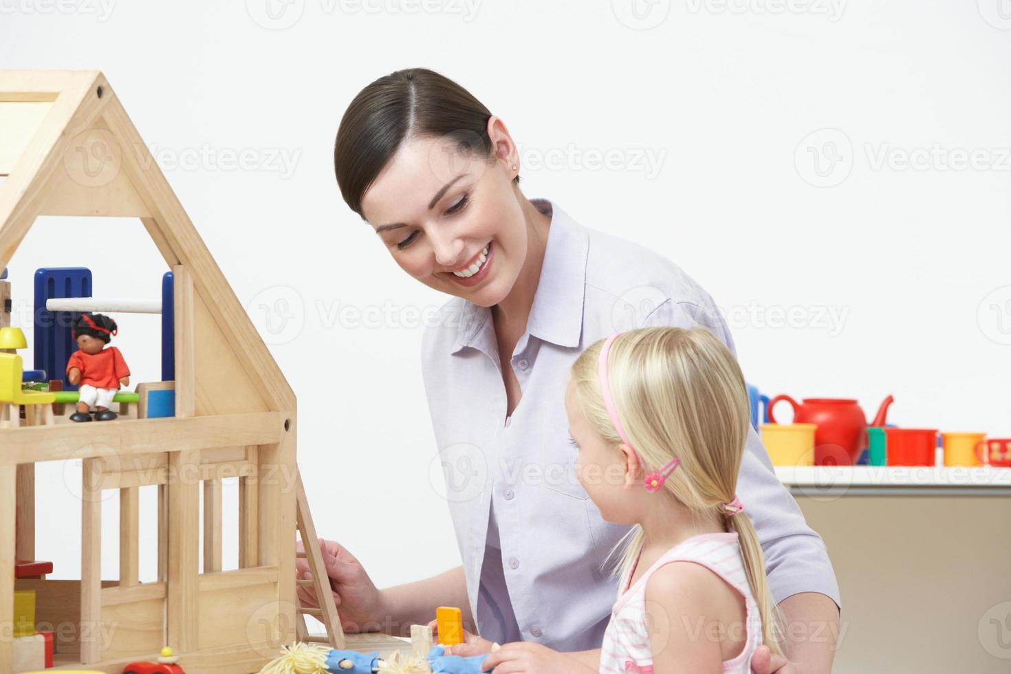 enseignant préscolaire et élève jouant avec maison en bois photo