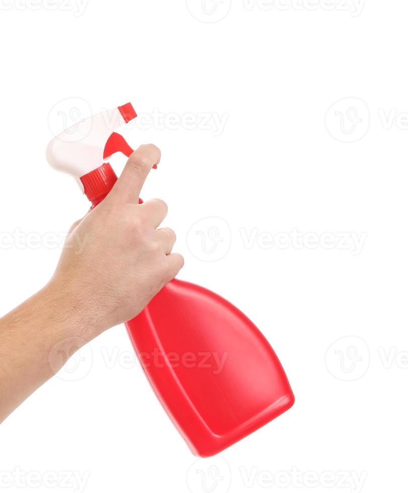 main tenant le flacon pulvérisateur en plastique rouge. photo