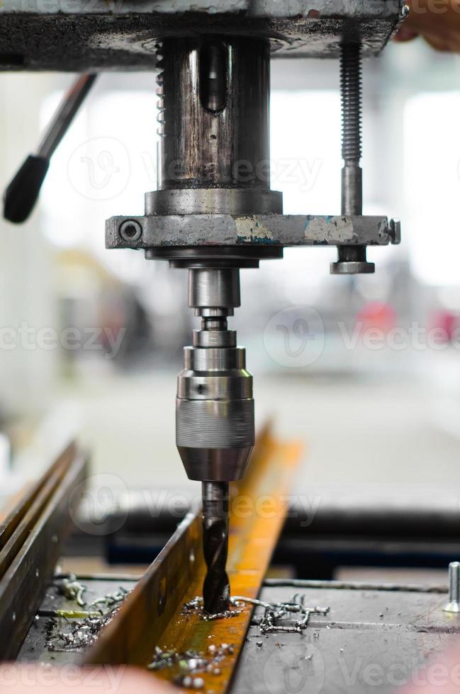 ingénieur industriel à l'aide d'une perceuse mécanique photo