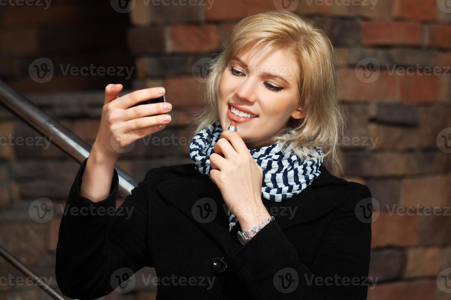 heureuse jeune femme tenant un rouge à lèvres photo