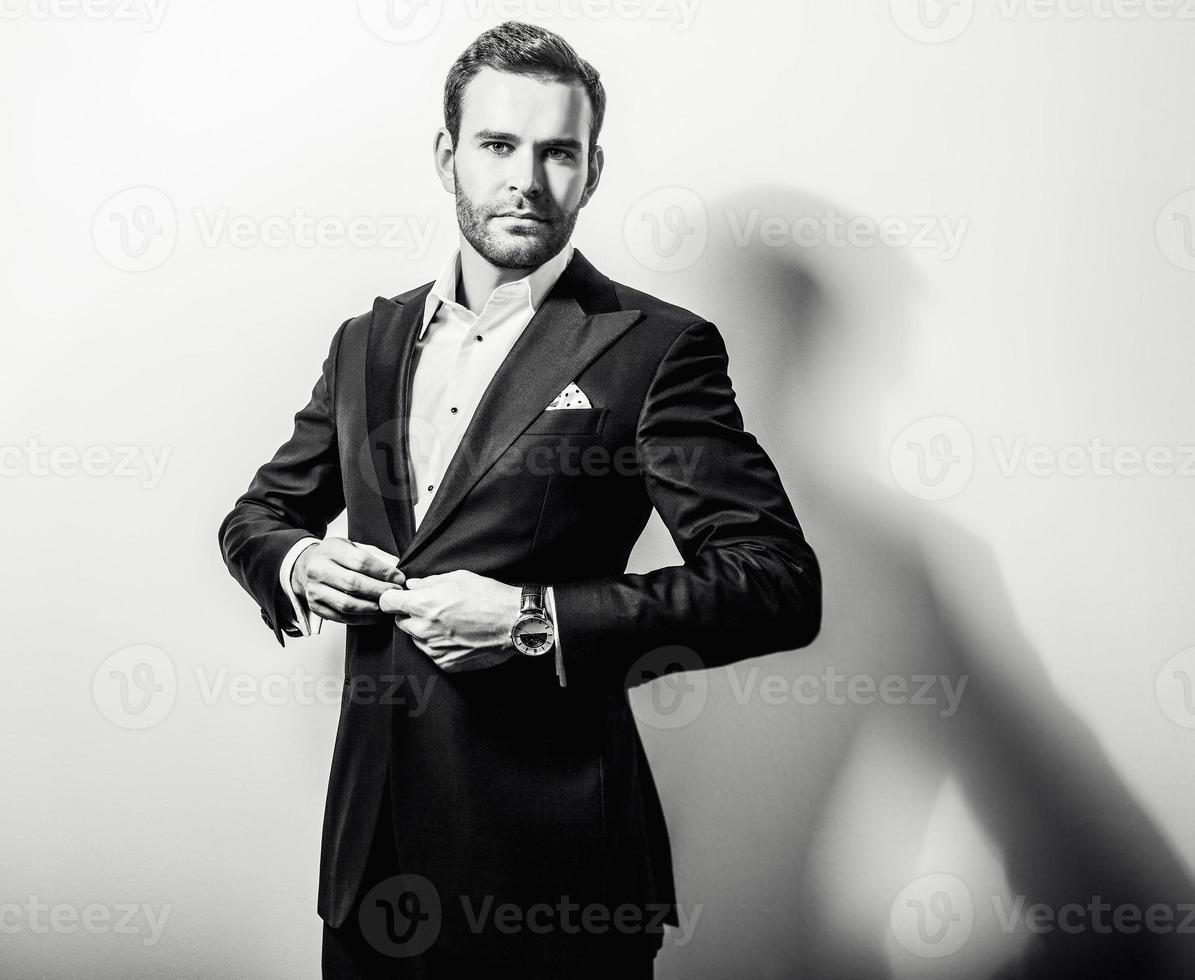 élégant jeune bel homme en costume noir classique. photo