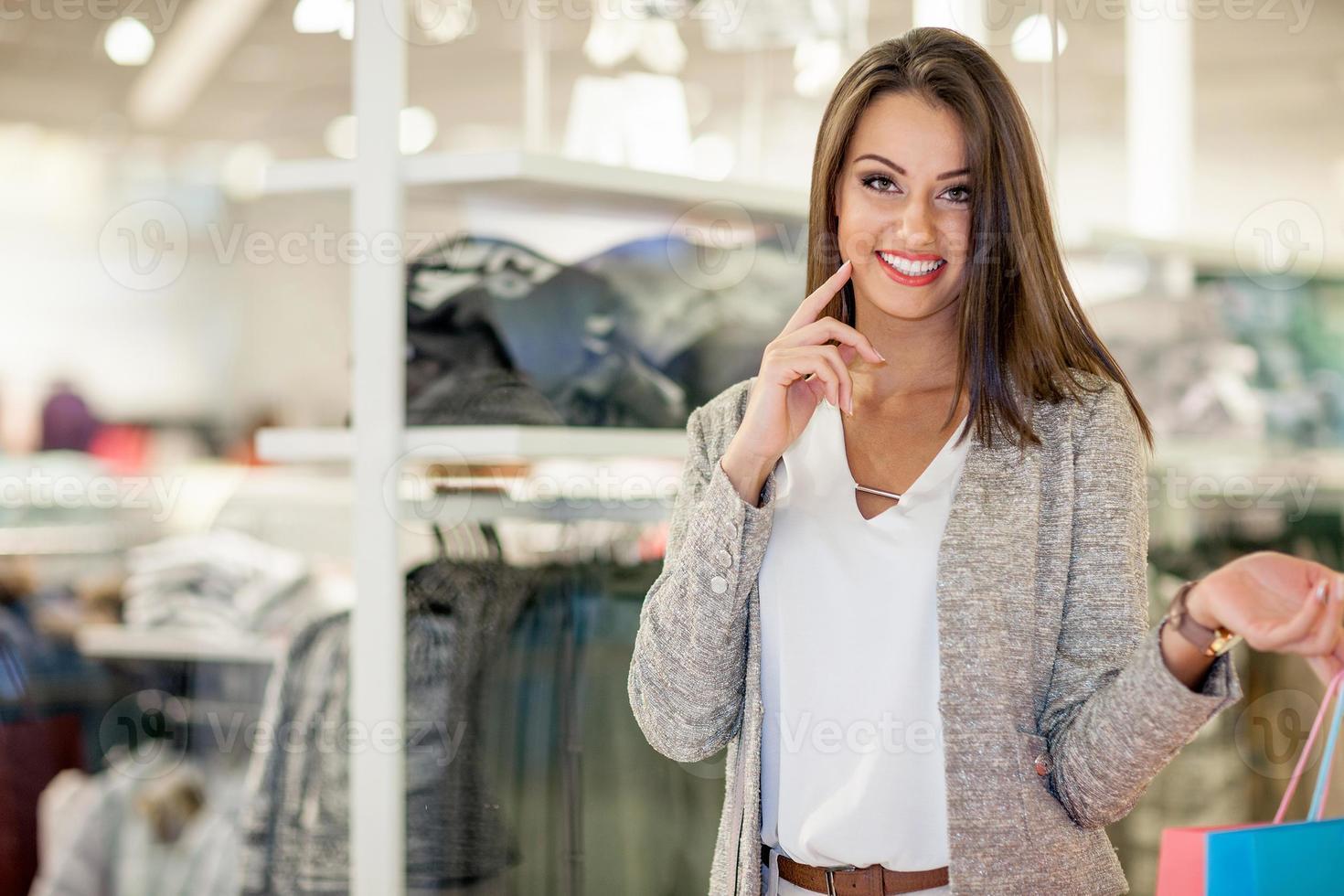 Souriante jeune femme avec des sacs à provisions sur fond de centre commercial photo
