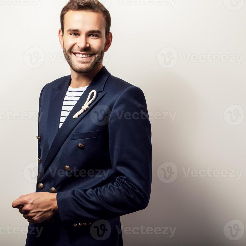 élégant jeune bel homme positif en costume bleu foncé. photo