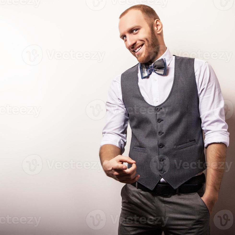 élégant jeune bel homme en gilet gris et noeud papillon. photo