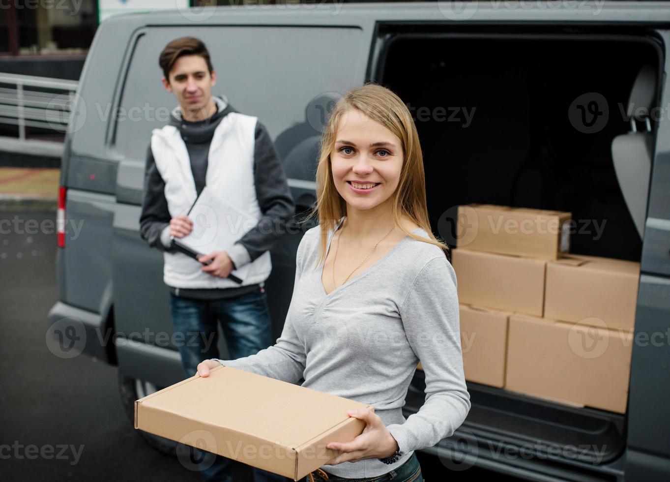 femme heureuse reçoit un colis du service de livraison. photo