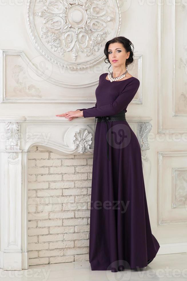 femme en élégante robe longue violette en studio photo