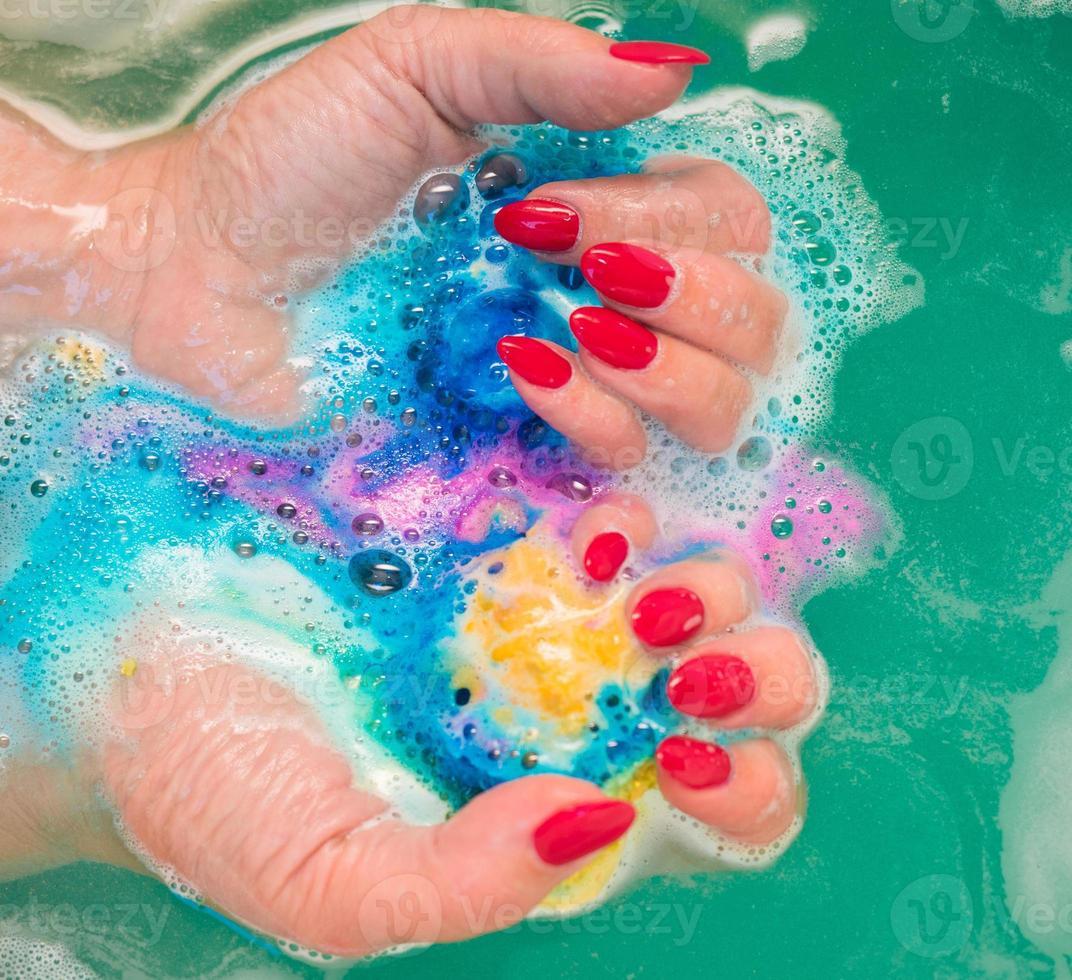 ongles manucurés rouges dans une mousse de savon photo