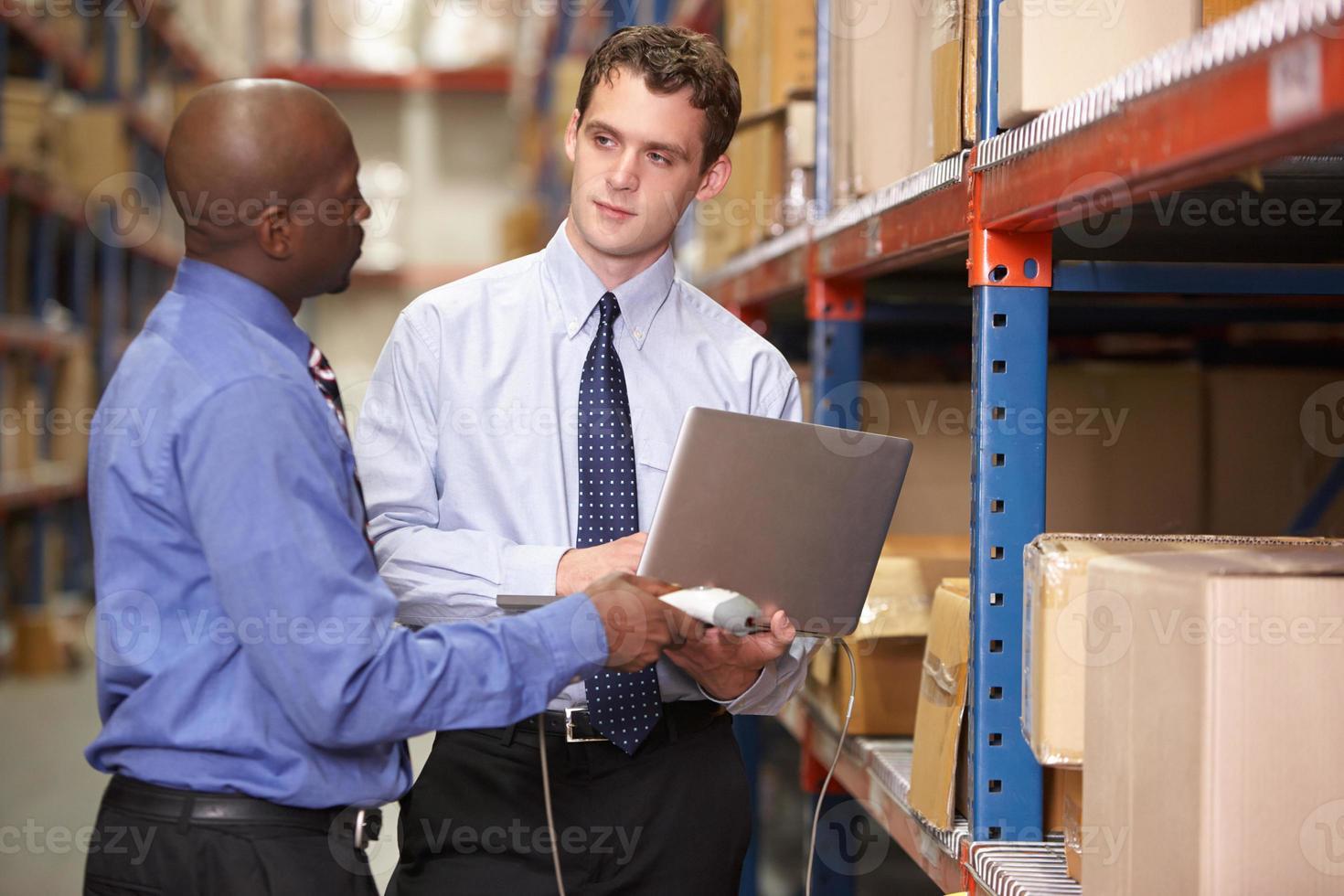 deux hommes d'affaires avec ordinateur portable en entrepôt photo