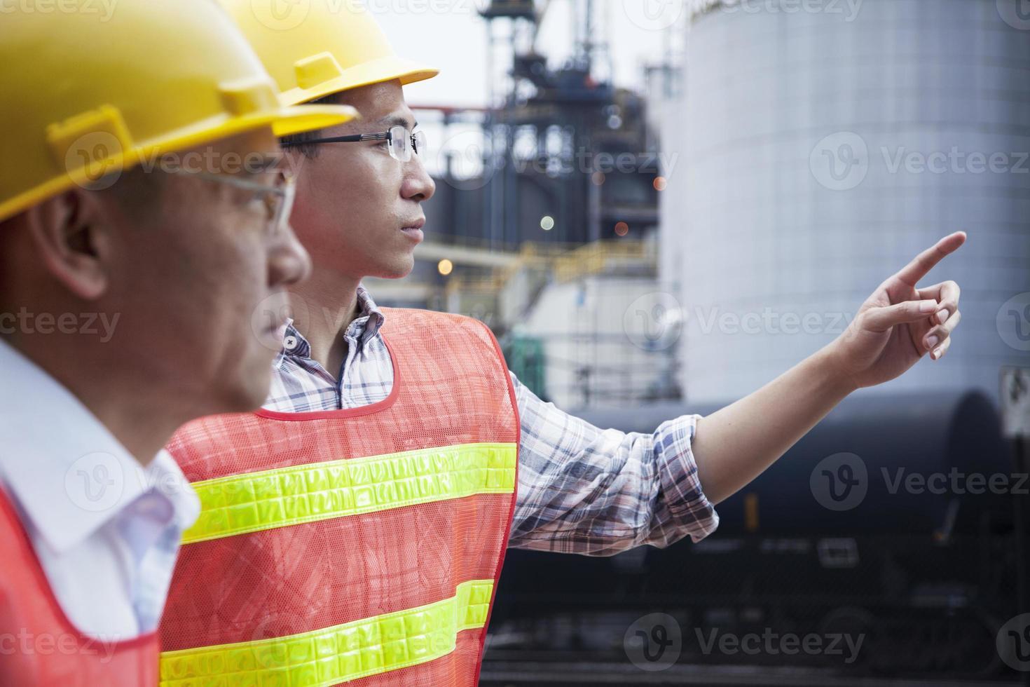 deux ingénieurs en vêtements de travail de protection pointant à l'extérieur d'une usine photo