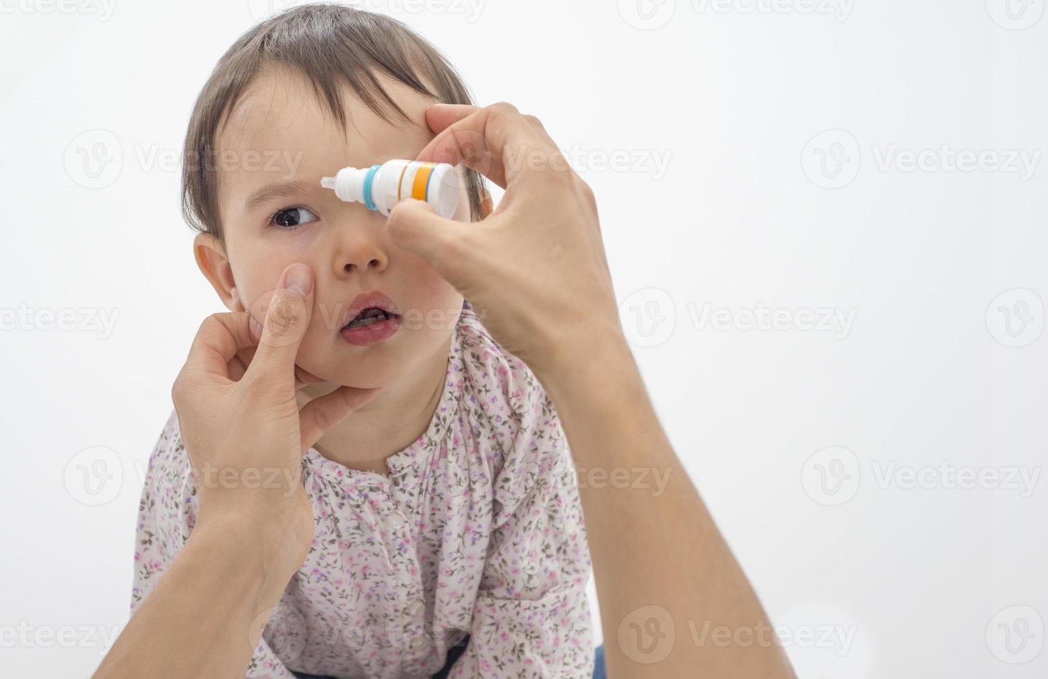 mère, verser des gouttes pour les yeux dans les yeux de sa fille photo