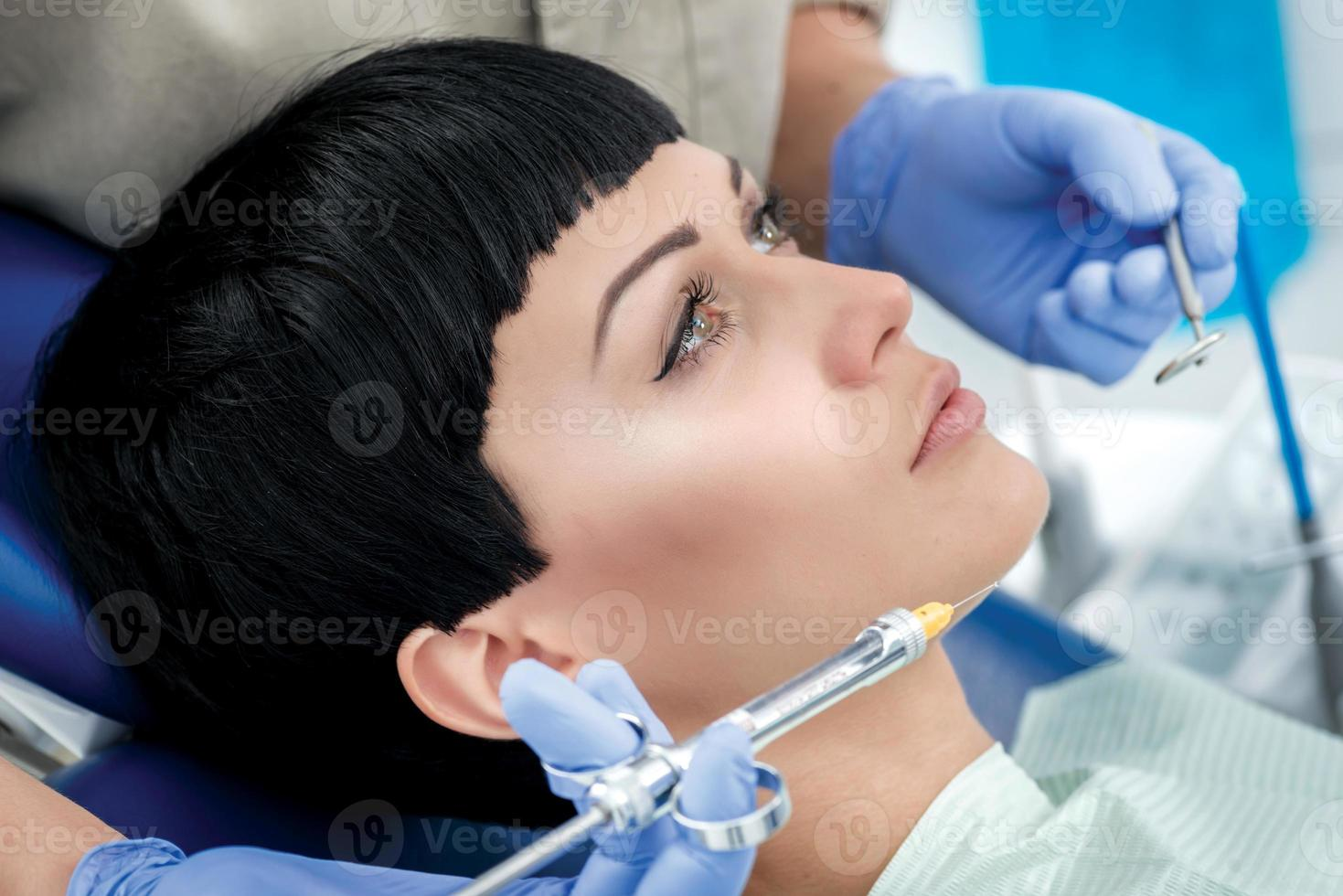 seringue avec anesthésie près des joues dentiste client. dentiste photo