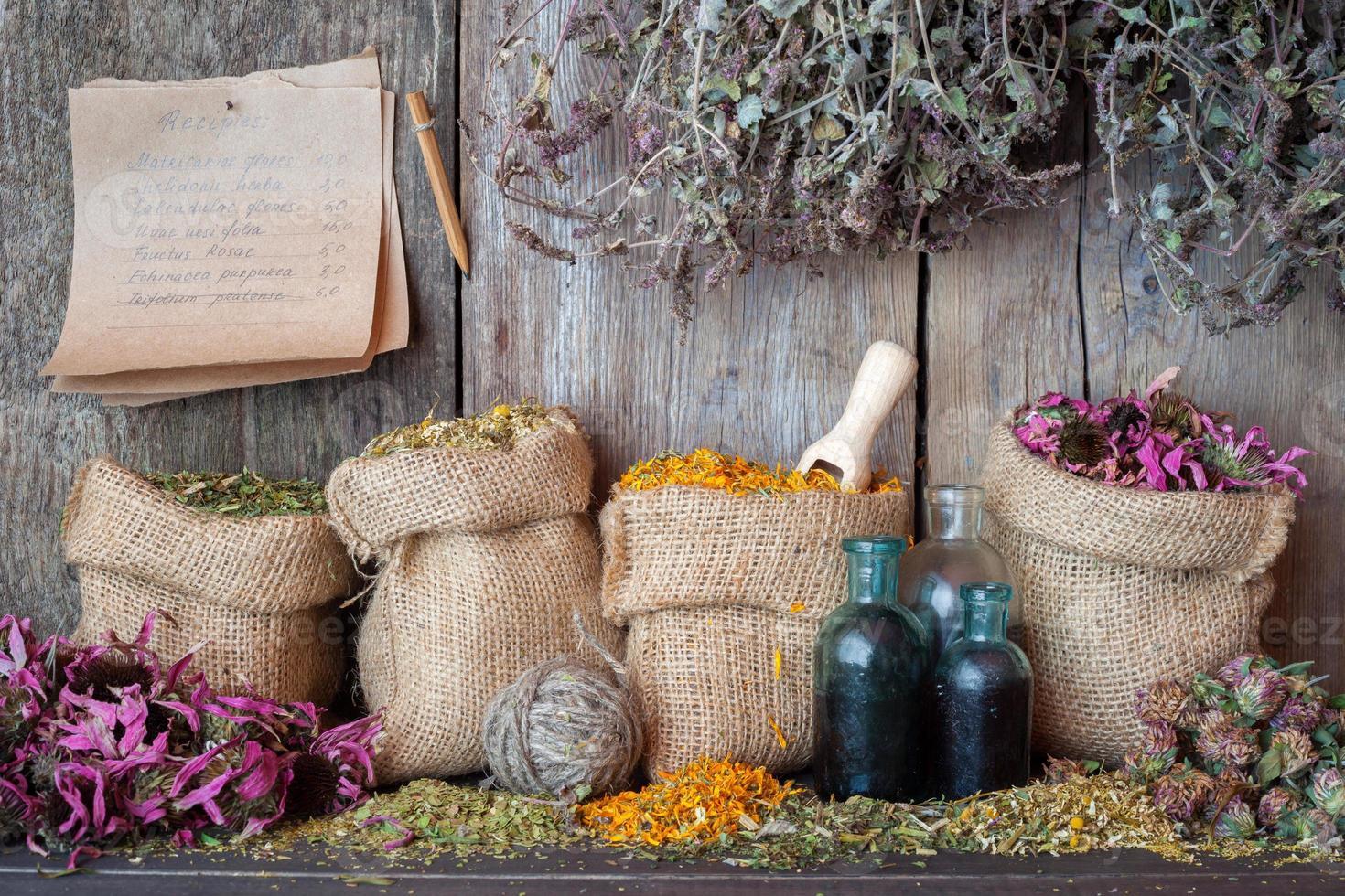 herbes médicinales dans des sacs en toile de jute près d'un mur en bois. photo