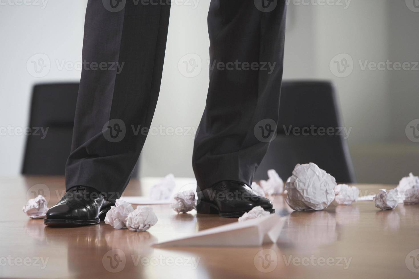 jambes sur la table de conférence avec des papiers froissés photo