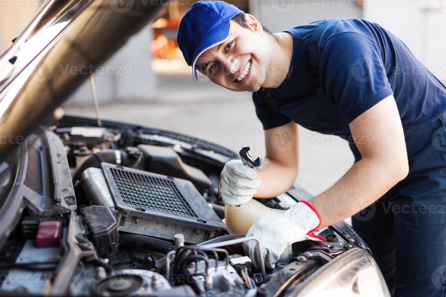 mécanicien fixant un moteur de voiture photo