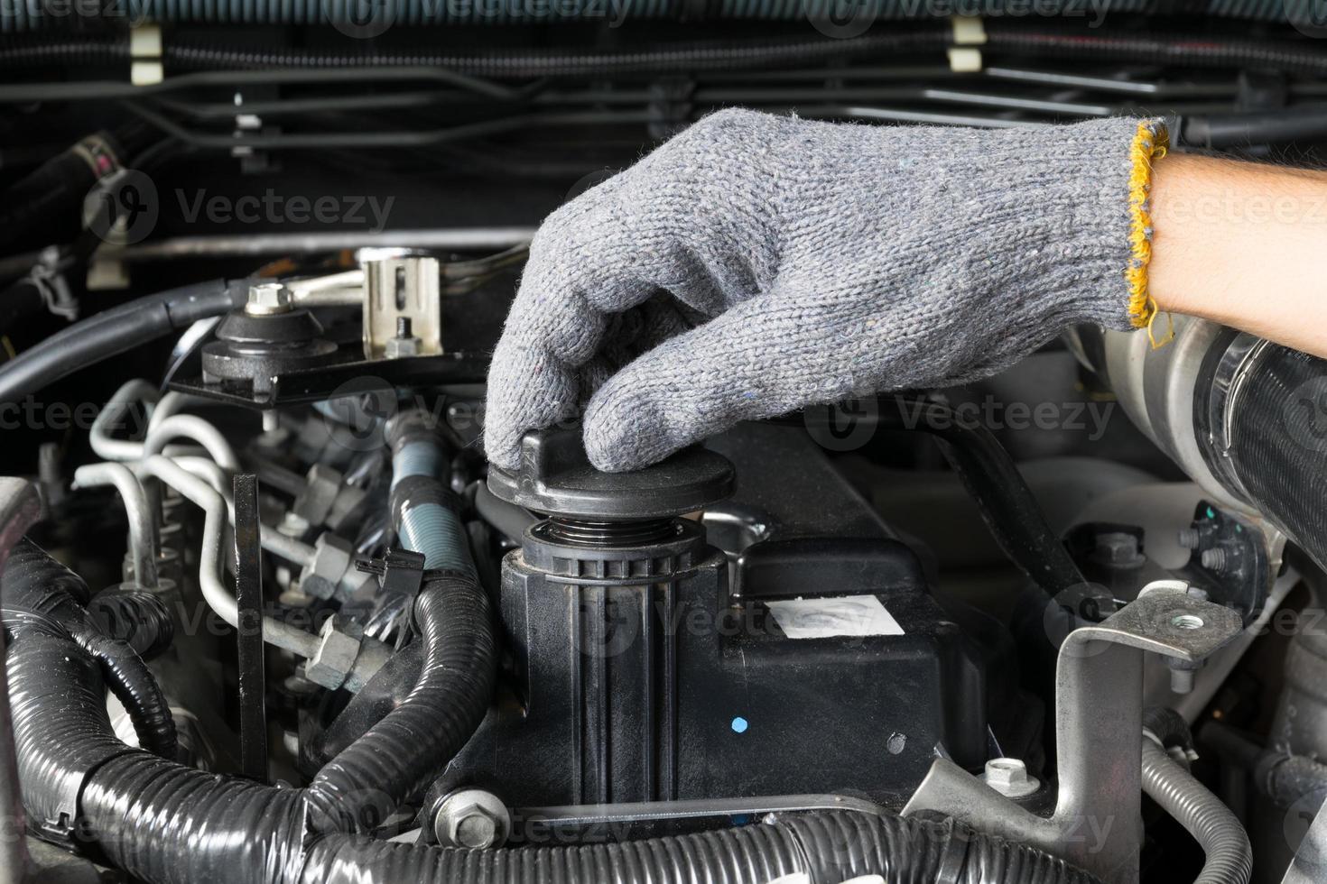 mécanicien ouvre le bouchon d'huile d'un moteur de voiture. photo