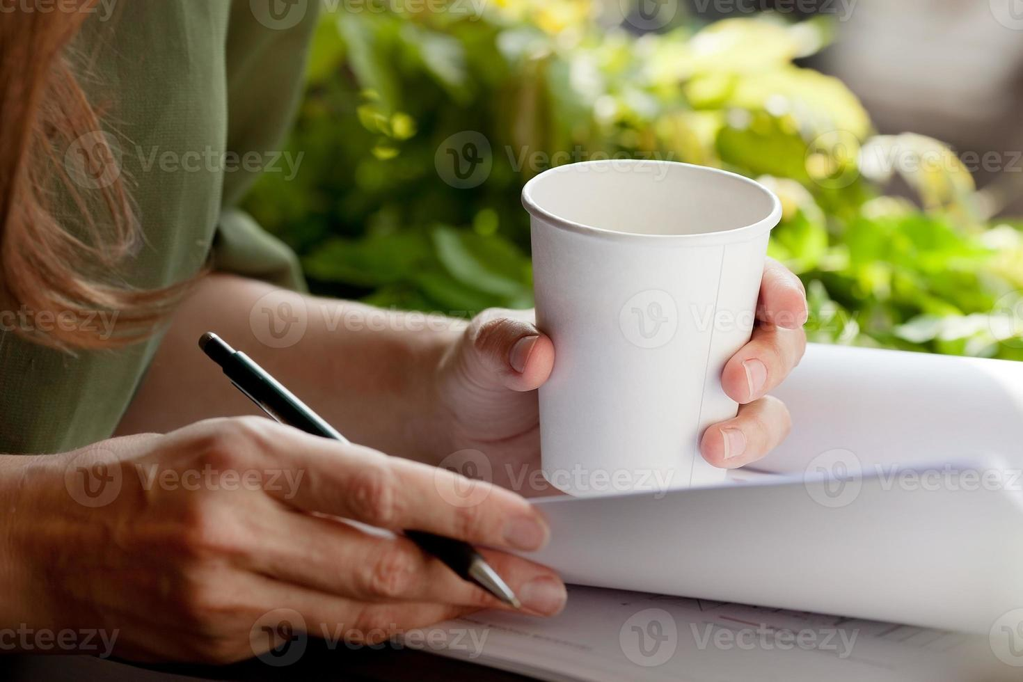 jeune femme au travail, boire du café dans une tasse jetable. photo