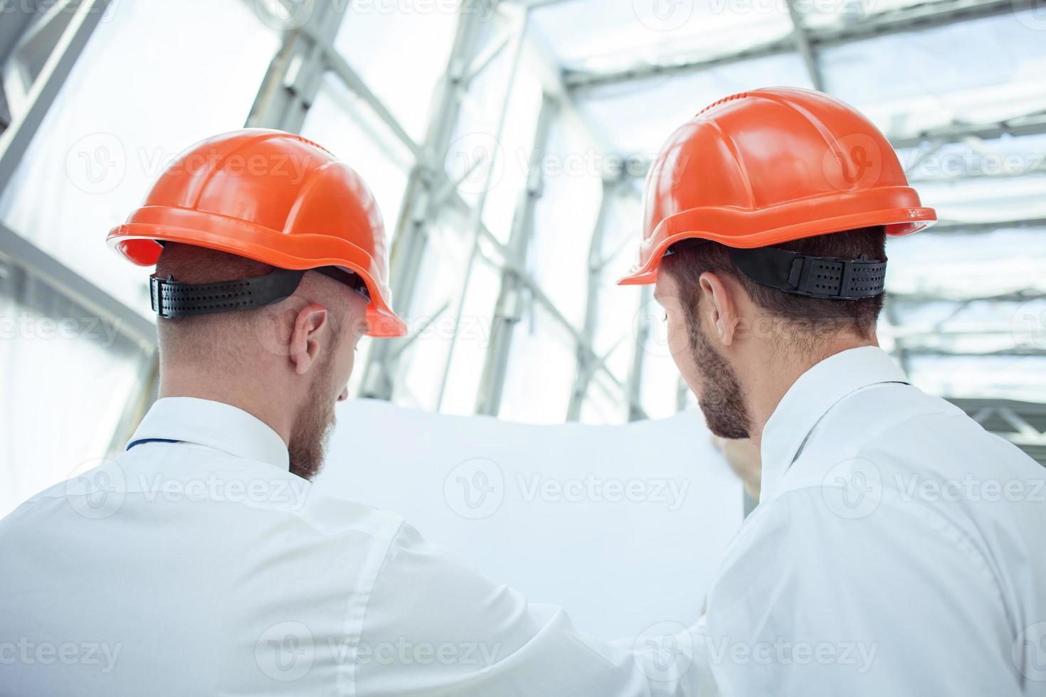 jeunes constructeurs gais travaillent sur le plan de construction photo