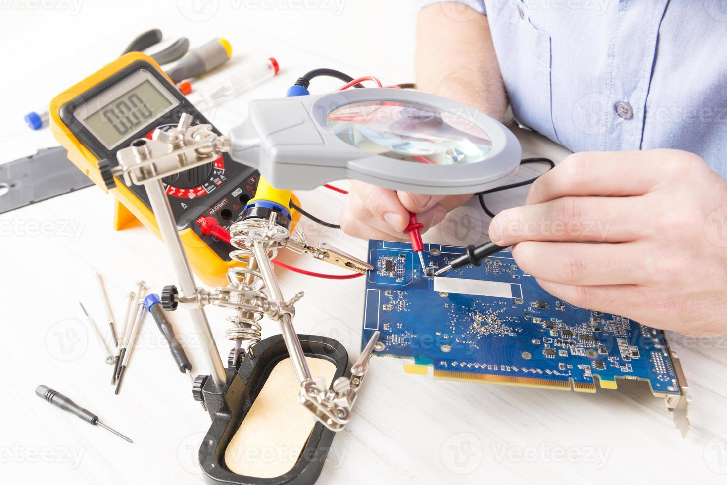 militaire vérifie le circuit imprimé avec un multimètre numérique photo