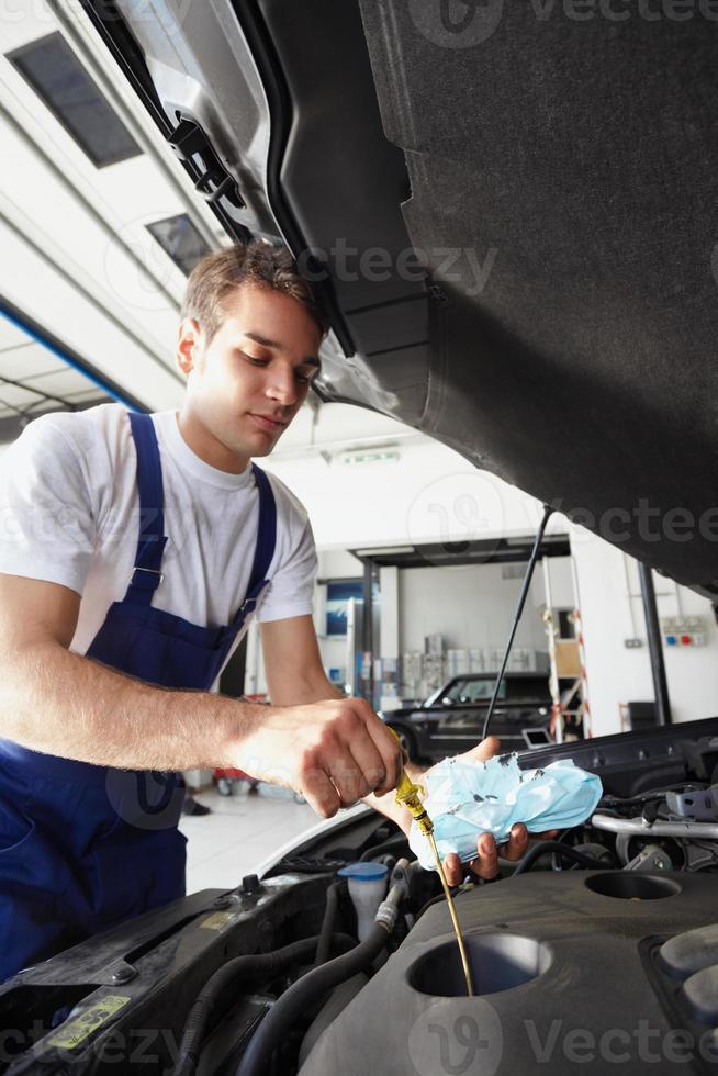 mécanicien au travail, vérification du niveau d'huile sur le moteur d'une voiture photo