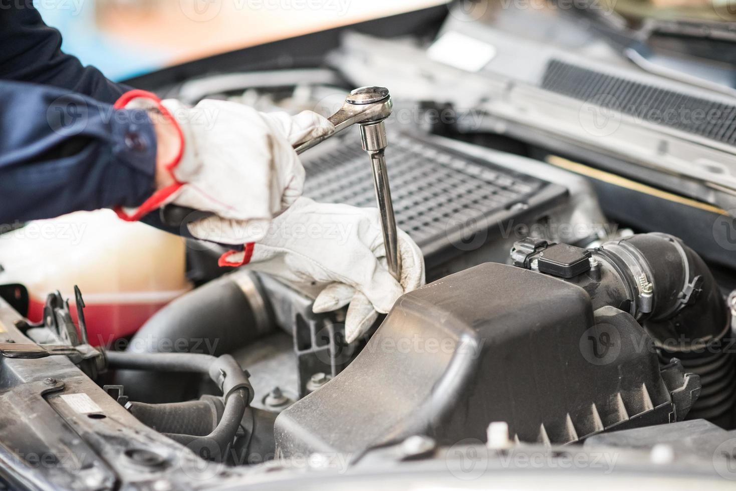 mécanicien automobile travaillant sur une voiture dans son garage photo