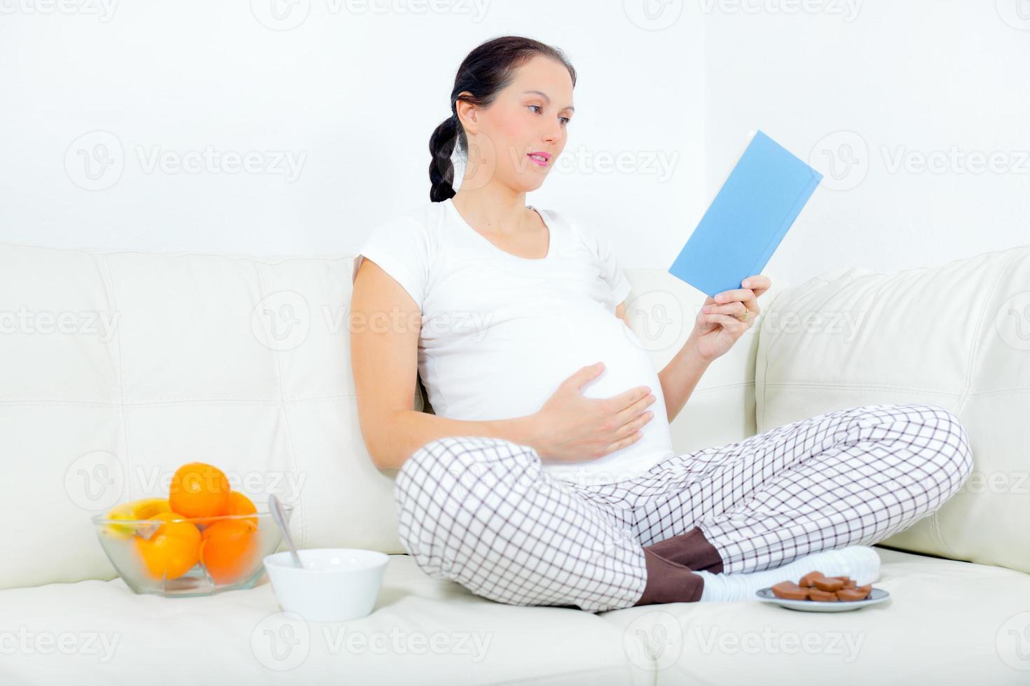 femme enceinte reposant sur le canapé, lisant un livre. photo
