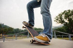 skateboarder à cheval sur la planche à roulettes au skatepark photo