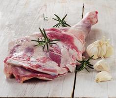 cuisse d'agneau cru sur une planche à découper en bois. photo
