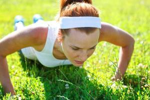 jeune femme faisant des pompes sur l'herbe verte. photo