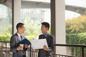 deux jeunes hommes d'affaires travaillant en plein air, se regardant photo